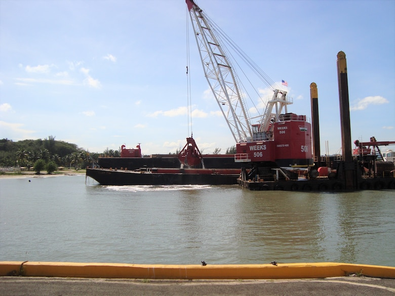 a red dredge with the claw lifted off the water