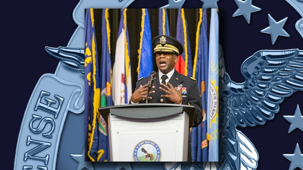 Army Lt. Gen. Darrell K. Williams delivers a keynote address from behind a lectern with flags in the background.
