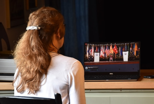A woman is seated watching a streaming video of a keynote address from a laptop