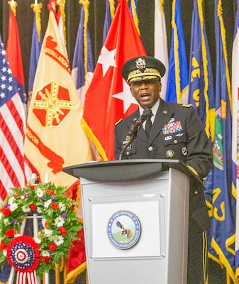 Army Lt. Gen. Darrell K. Williams delivered a keynote address behind a lectern with flags in the background.