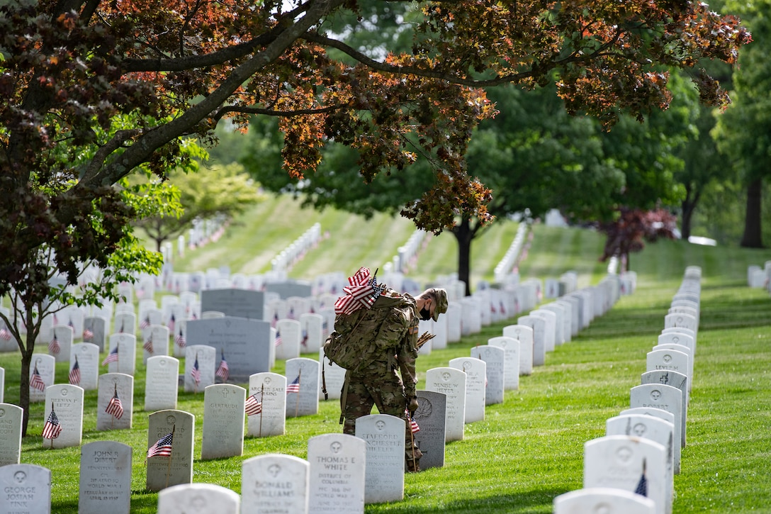 A soldier places a small American flag in front of a headstone.