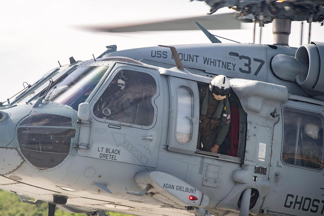 Sailors fly in a helicopter.