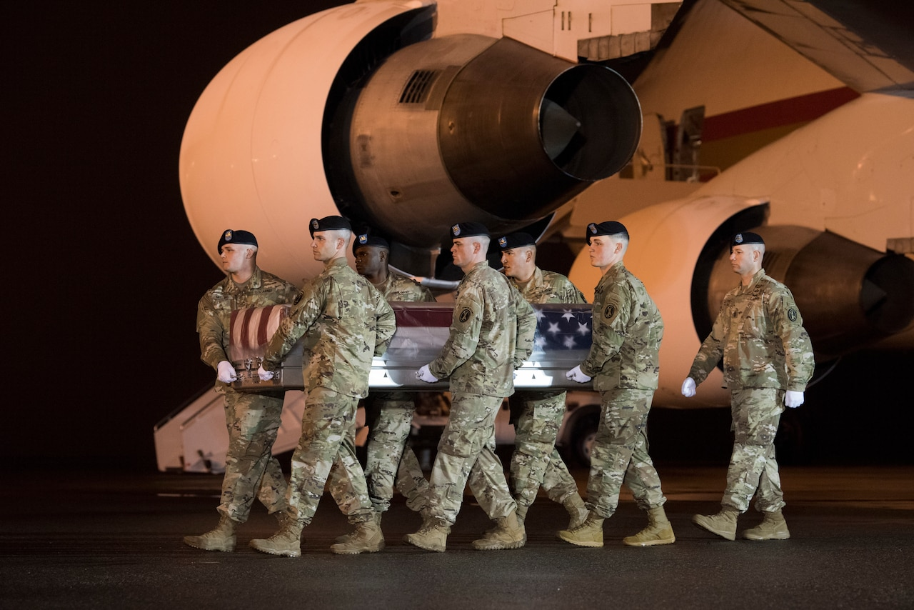 Soldiers carry casket off aircraft.