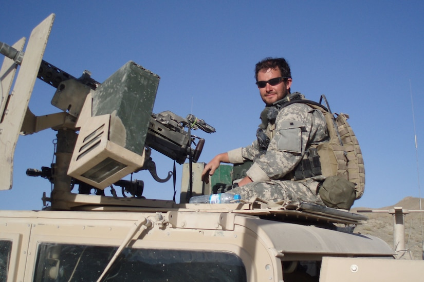 A soldier sits behind a gun mounted to a Humvee.