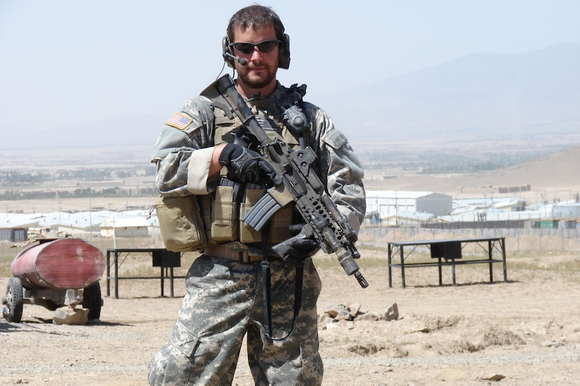 A soldier poses with his weapon in a desert town.