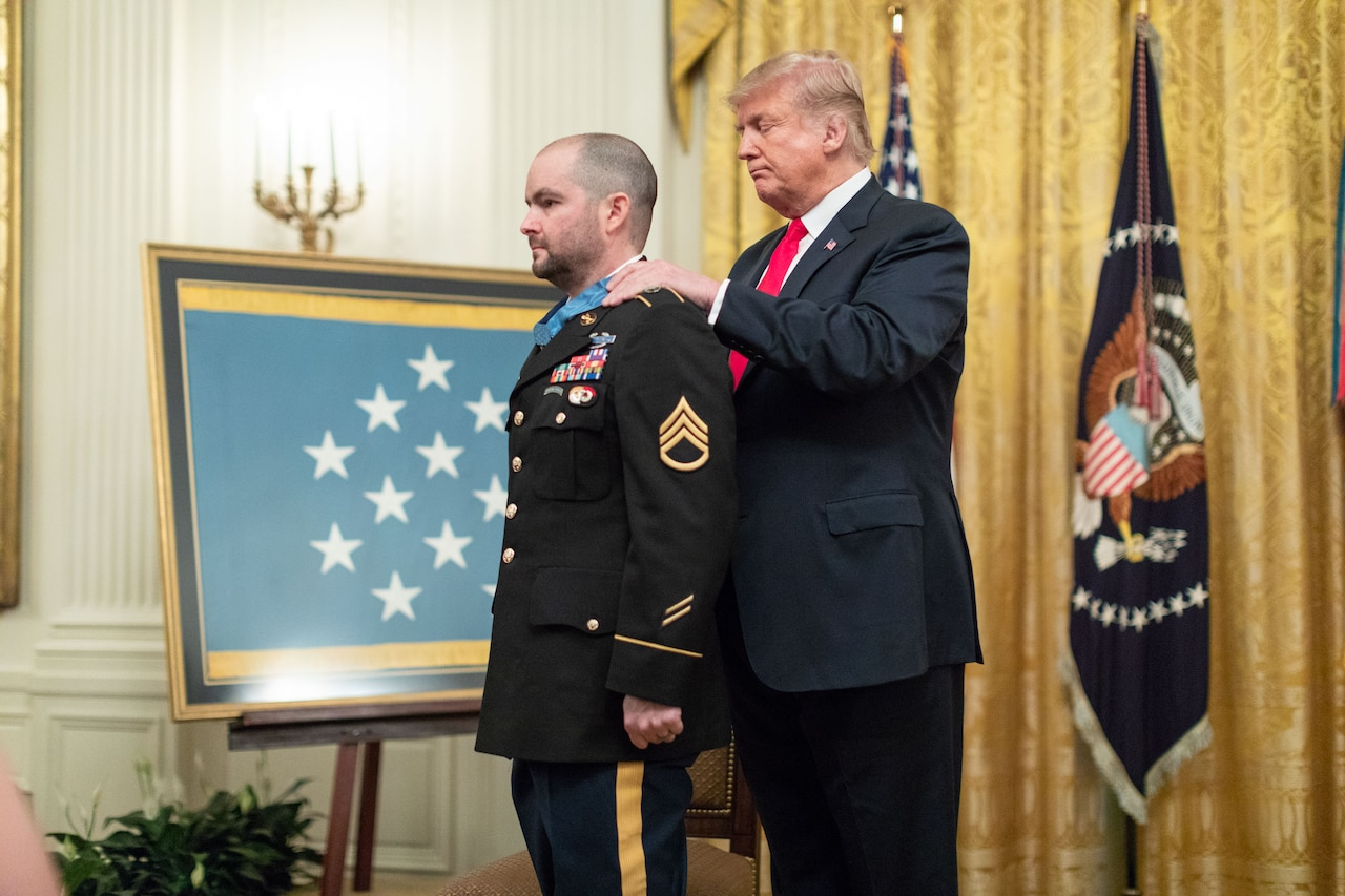 A man places a medal around a uniformed man's neck.