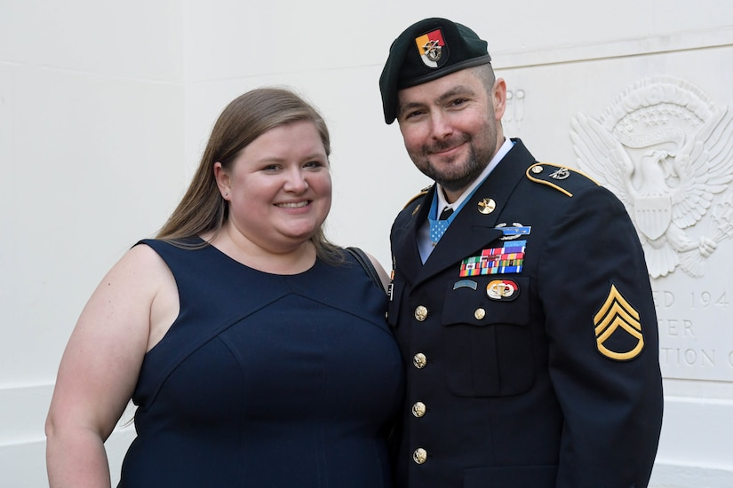 A woman and a man in uniform pose for a photo.