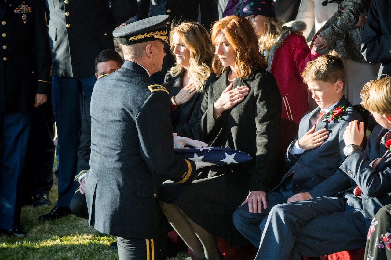 Officer kneels to present folded U.S. flag to widow,