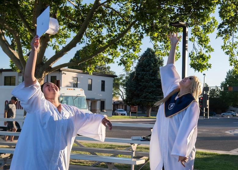 Graduates toss their caps in the air.