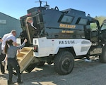 Deputies help residents exit an armored vehicle.