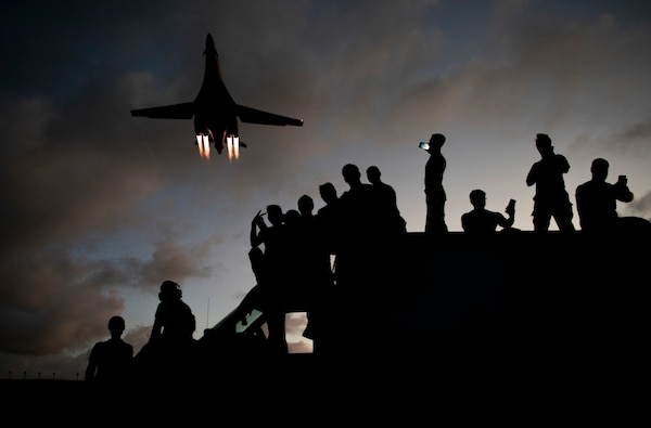 9th Expeditionary Bomb Squadron B-1B Lancer mechanics take selfies as a B-1B flies overhead at Andersen Air Force Base, Guam, May 21, 2020. In continued demonstration of the U.S. Air Force's dynamic force employment model, two U.S. Air Force B-1B Lancers flew from Andersen AFB and conducted training in Alaska and near Misawa Air Base, Japan.
