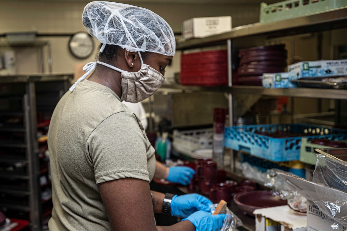 An airman in protective gear prepares food.