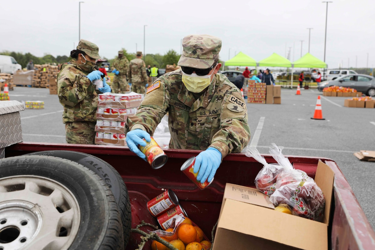 A soldier drops canned goods into a vehicle.