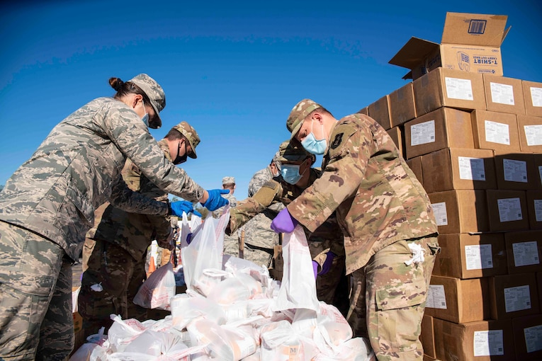 A group of airmen hold plastic bags.