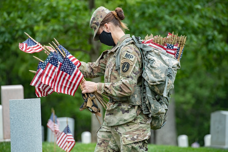 A soldier wearing a face mask walks through a cemetery carrying small American flags.
