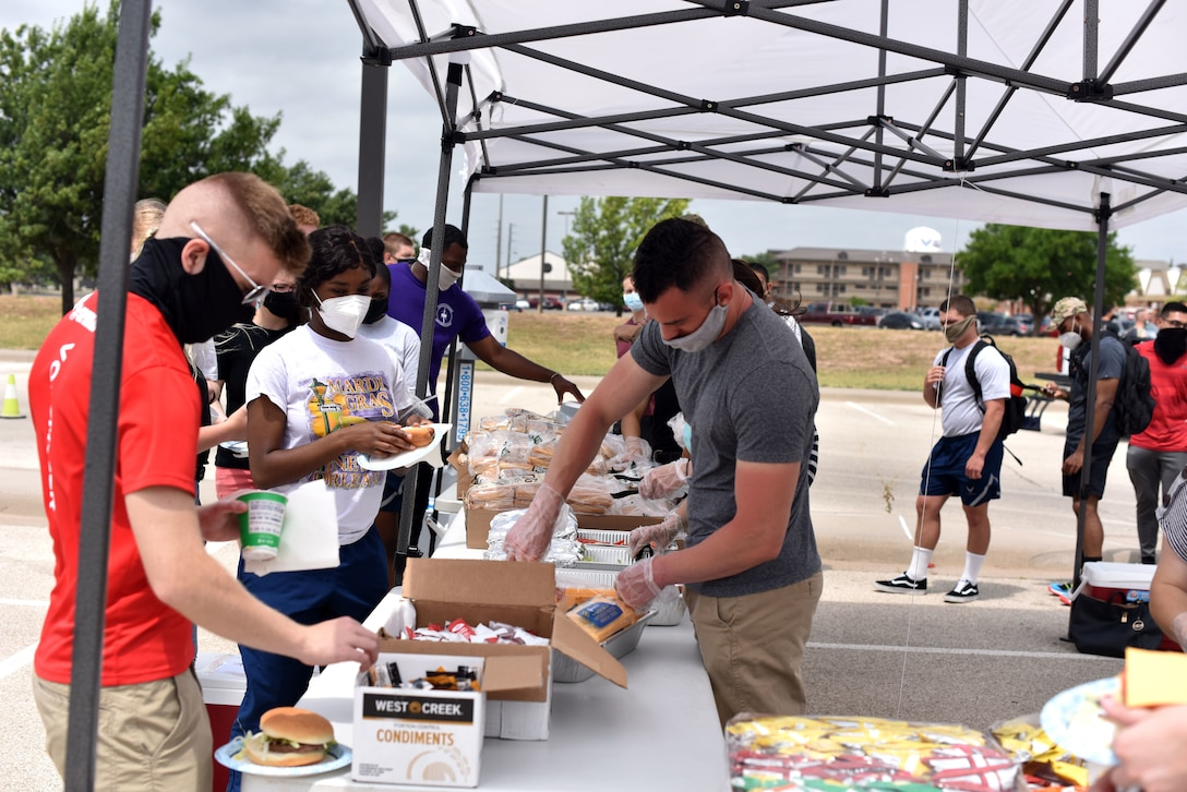 Goodfellow students go down the serving line receiving their hotdogs and hamburgers during the Memorial Day BBQ at the Crossroads on Goodfellow Air Force Base, Texas, May 23, 2020. While observing guidelines from the Centers for Disease Control and Prevention students spent time outside talking with chapel personnel and first sergeant members. (U.S. Air Force photo by Senior Airman Seraiah Wolf)