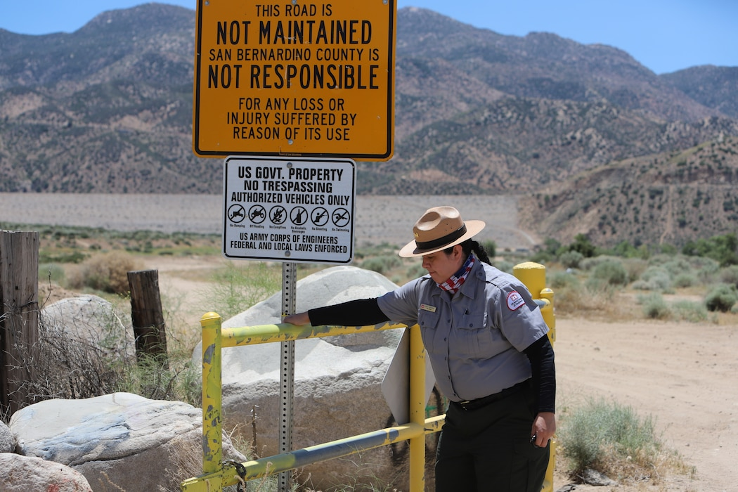 """U.S. Army Corps of Engineers Los Angeles District Park Ranger Mary Carmona secures the gate at the Deep Creek road entrance May 17. Vandals have continually cut the locks and removed the chains that secure that gate at several of the Corps Mojave River Dam basins entrances in the County of San Bernardino. The area also known as the """"Deep Creek Spillway"""" is located on federal property and is restricted to authorized motor vehicles and personnel."""