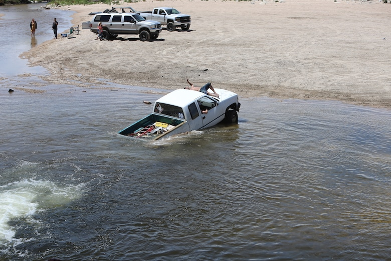 Driver of this vehicle awaits help from other drivers after becoming submerged in the Mojave River Dam's outlet May 17.