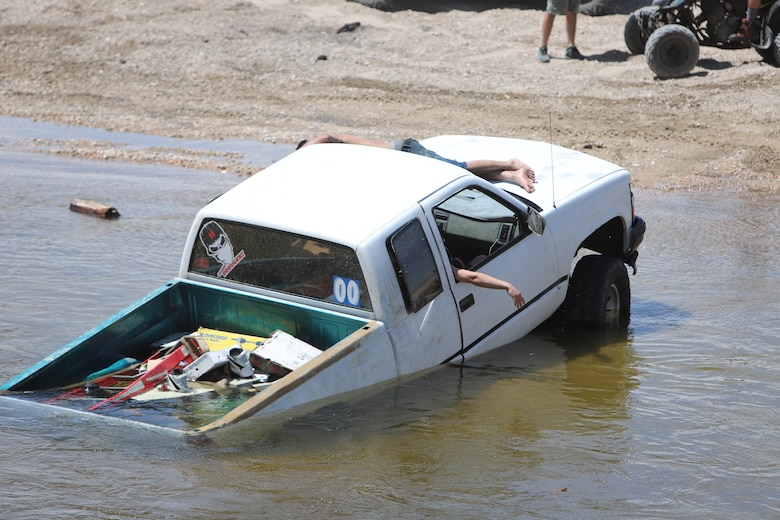Driver of this vehicle awaits help from other drivers to pull their vehicle from the Mojave River Dam's water outlet May 17.