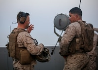 200521-M-MV109-1181 ARABIAN GULF (May 21, 2020) Capt. Richard Webb, fire support officer, left, and Cpl. Alexander Vogel, fire support Marine, assigned to Headquarters Company, Battalion Landing Team 2/8, 26th Marine Expeditionary Unit (MEU), discuss communications during an aviation operation in support of sea control training evolution aboard the amphibious transport dock USS New York (LPD 21) May 21, 2020. New York, with embarked 26th MEU, is deployed to the U.S. 5th Fleet area of operations in support of naval operations to ensure maritime stability and security in the Central Region, connecting the Mediterranean and Pacific through the Western Indian Ocean and three strategic choke points. (U.S. Marine Corps photo by Staff Sgt. Patricia A. Morris)