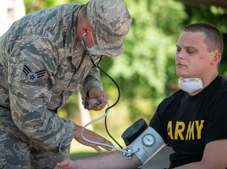 Senior Airman Tristan Kirk, a medic for Team 3 with Task Force 31, checks the vitals of a disinfection team specialist, May 1, 2020. The vitals of all Task Force 31 disinfection teams are checked before and after all disinfection operations. (Photo by U.S. Army Sgt. Jaccob Hearn)
