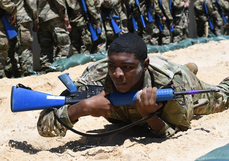 Airmen crawls in sand with rifle