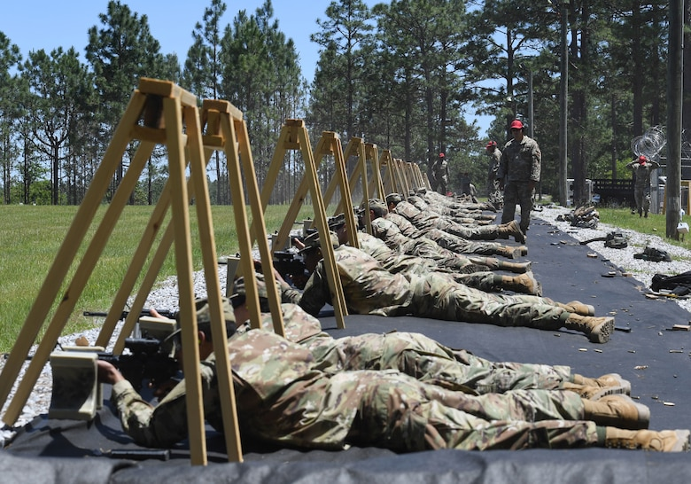 Airmen lay on ground firing weapons
