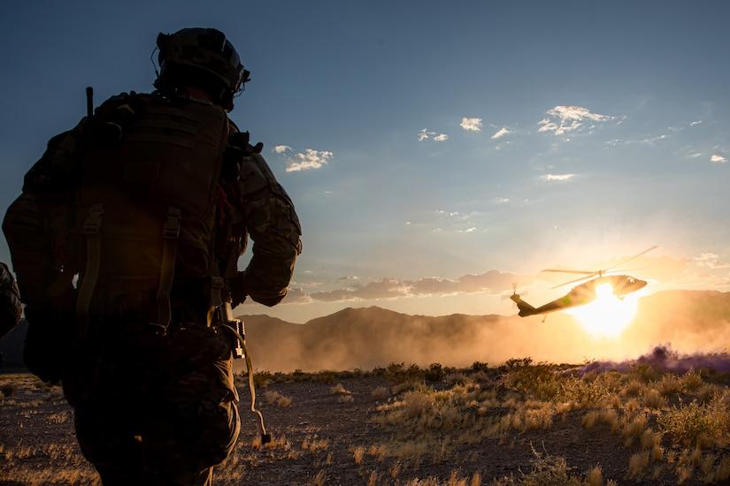 A Green Beret walks towards a landing helicopter.