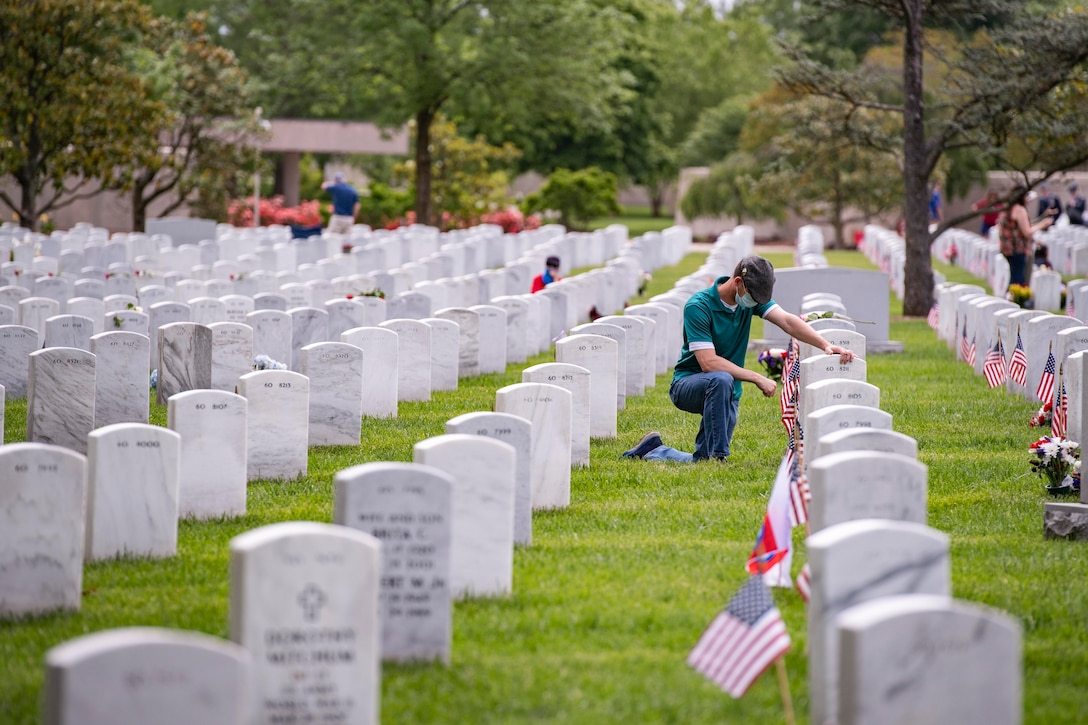 A man kneels down in front of a tombstone at a gravesite.