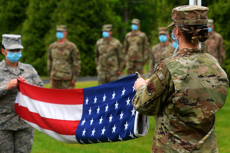 Airmen in masks fold a flag at a retreat ceremony.