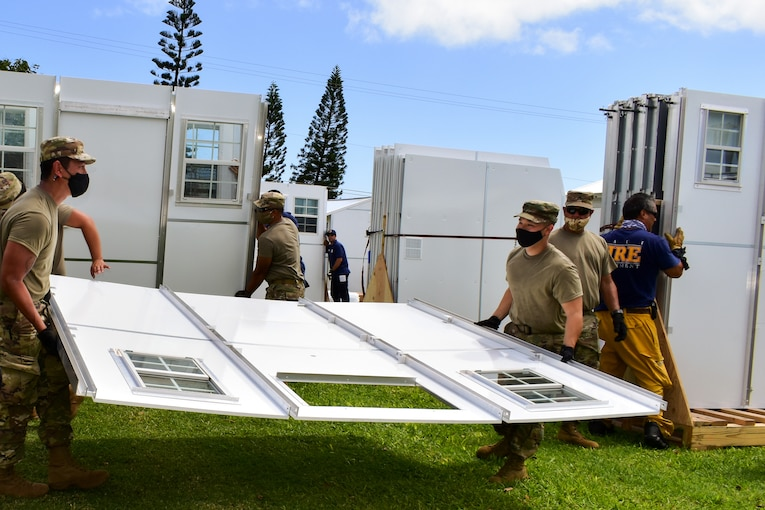 Service members and civilians construct temporary shelters for residents.