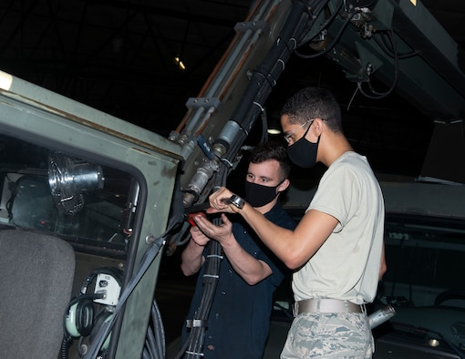 Two Airmen working on fly-cab of a deicer, turning wrenches