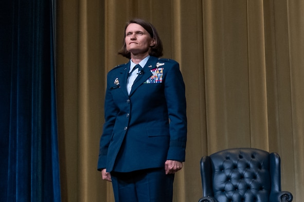 Brigadier Gen. Leslie Maher stands at attention on a stage during her assumption of command ceremony.