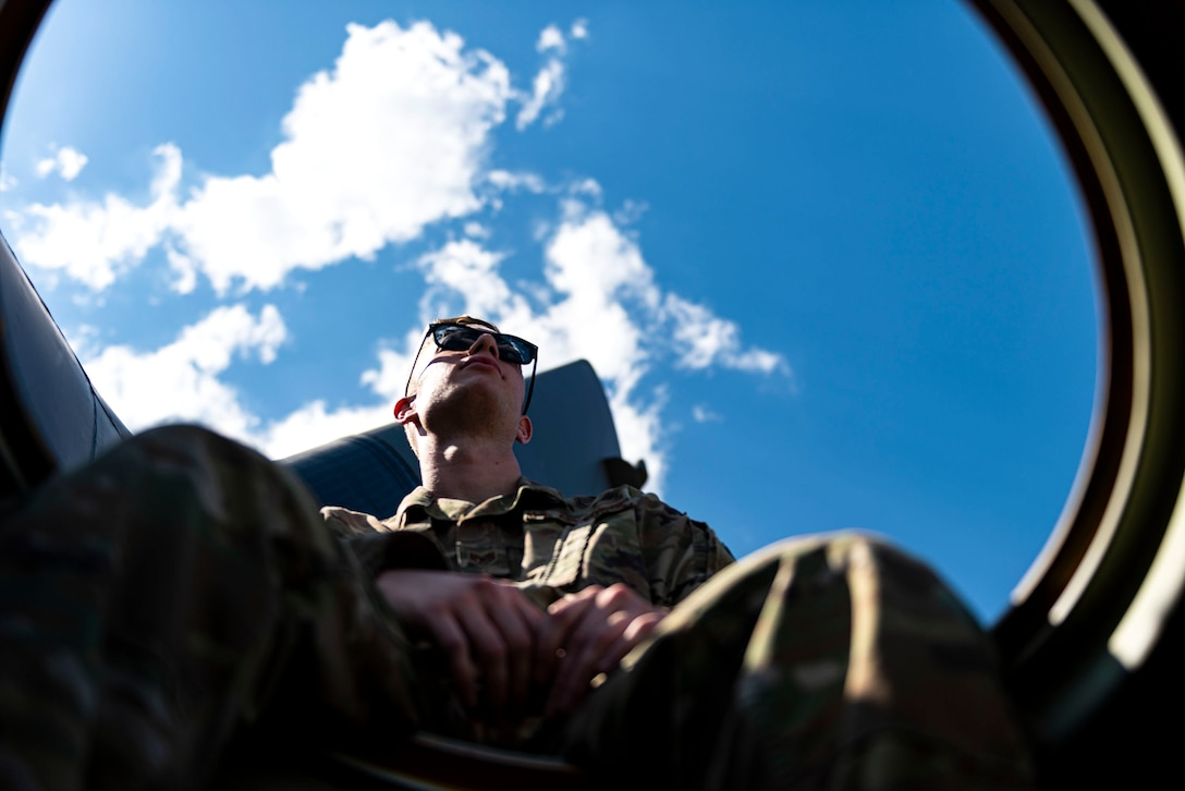 Photo of Airman looking out of an HC-130J Combat King II.