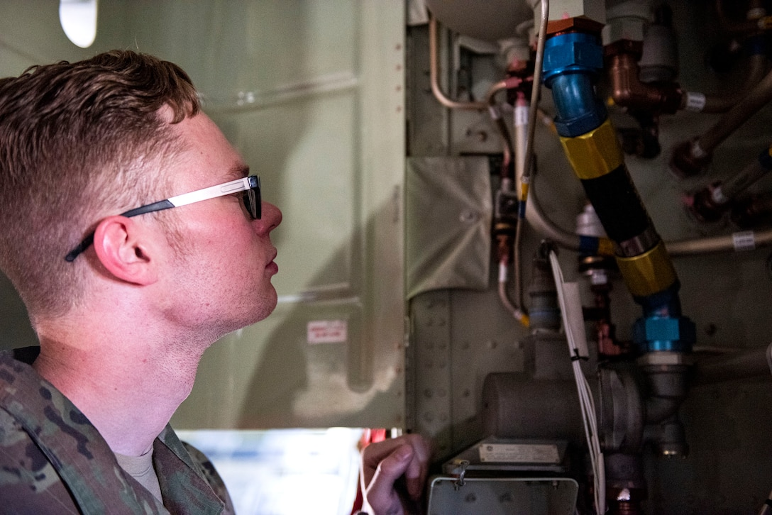 Photo of Airman examining a hydraulic system.