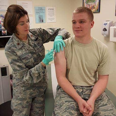 Maj. Natalie Keith, 403rd Aeromedical Staging Squadron clinical nurse, delivers an immunization to Tech. Sgt. Zach Barnhill, 403rd ASTS medical technician. (courtesy photo from Lt. Col. Natalie McKee/ released with Tech. Sgt. Barnhill's approval)