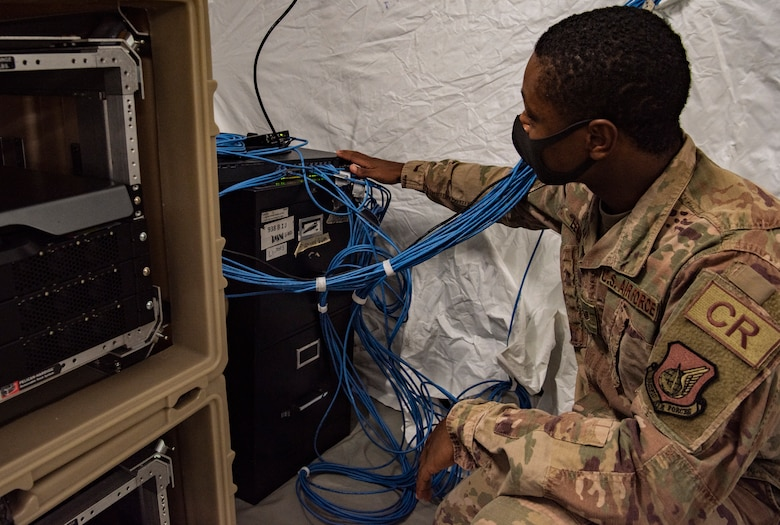 U.S. Air Force Staff Sgt. Curtis Lewis, 644th Combat Communications Squadron cyber transport supervisor, inspects a network server at the Expeditionary Medical Support System (EMEDS), located at Naval Hospital, Guam, May 13, 2020.