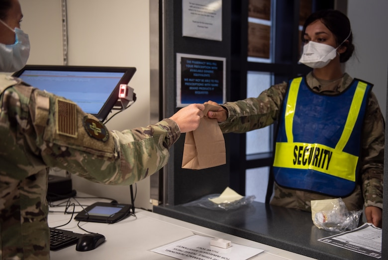 U.S. Air Force Tech Sgt. Amanda Dorsey (left), 36th Medical Support Squadron NCO in charge of pharmacy supply, gives medication to Senior Airman Patience Letourneau, 36th Medical Operations Squadron dental technician, at Andersen Air Force Base, Guam, May 16, 2020.