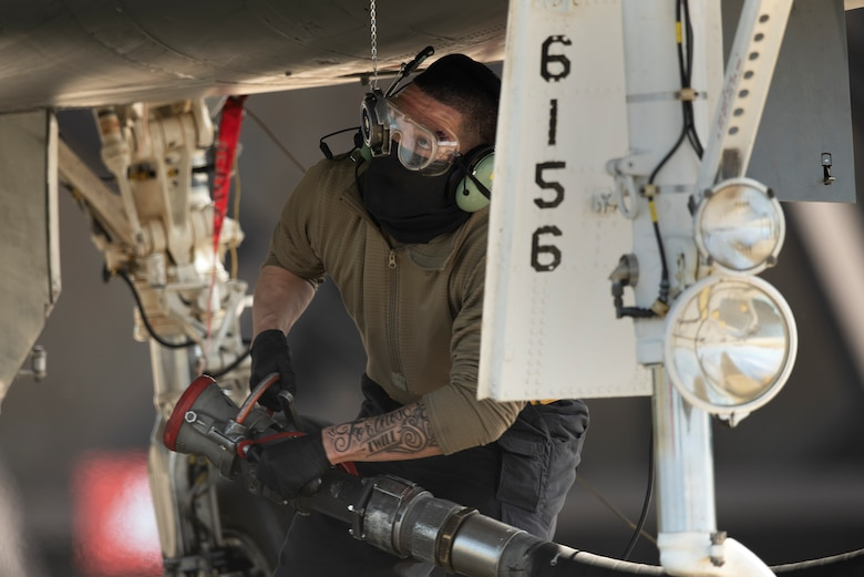 """A crew chief assigned to the 493rd Fighter Squadron Aircraft Maintenance Unit prepares to perform """"hot pit"""" refueling on an F-15C Eagle at Royal Air Force Lakenheath, England, May 20, 2020. Crew chiefs work closely with 48th Logistics Readiness Squadron Airmen to deliver over 350,000 gallons of JP-8 fuel per week, keeping the Liberty Wing ready to deliver combat airpower. (U.S. Air Force photo by Airman 1st Class Jessi Monte)"""