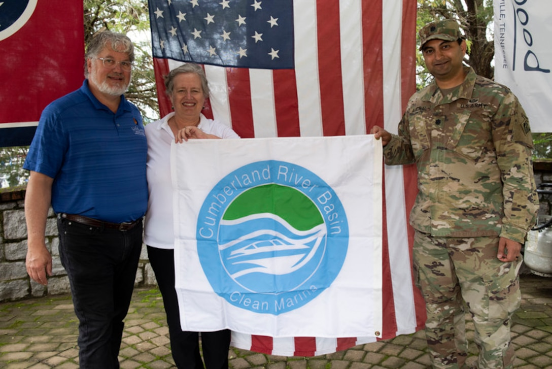"""Lt. Col. Sonny B. Avichal, U.S. Army Corps of Engineers Nashville District commander, presents the """"Clean Marina"""" flag to John and Natasha Deane, owners of Wildwood Resort and Marina, during a dedication May 21, 2020 at the resort located at Cordell Hull Lake in Granville, Tennessee.  The event recognized the marina's voluntary efforts to reduce water pollution and erosion in the Cumberland River watershed, and for promoting environmentally responsible marina and boating practices."""