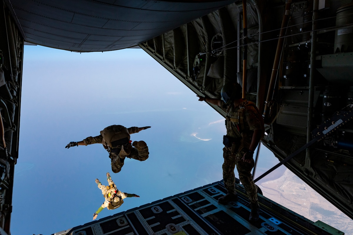 Two airmen jump from an aircraft.