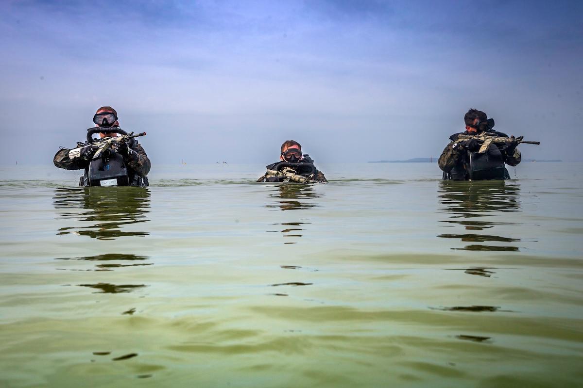 Three Marines wade through water carrying guns.