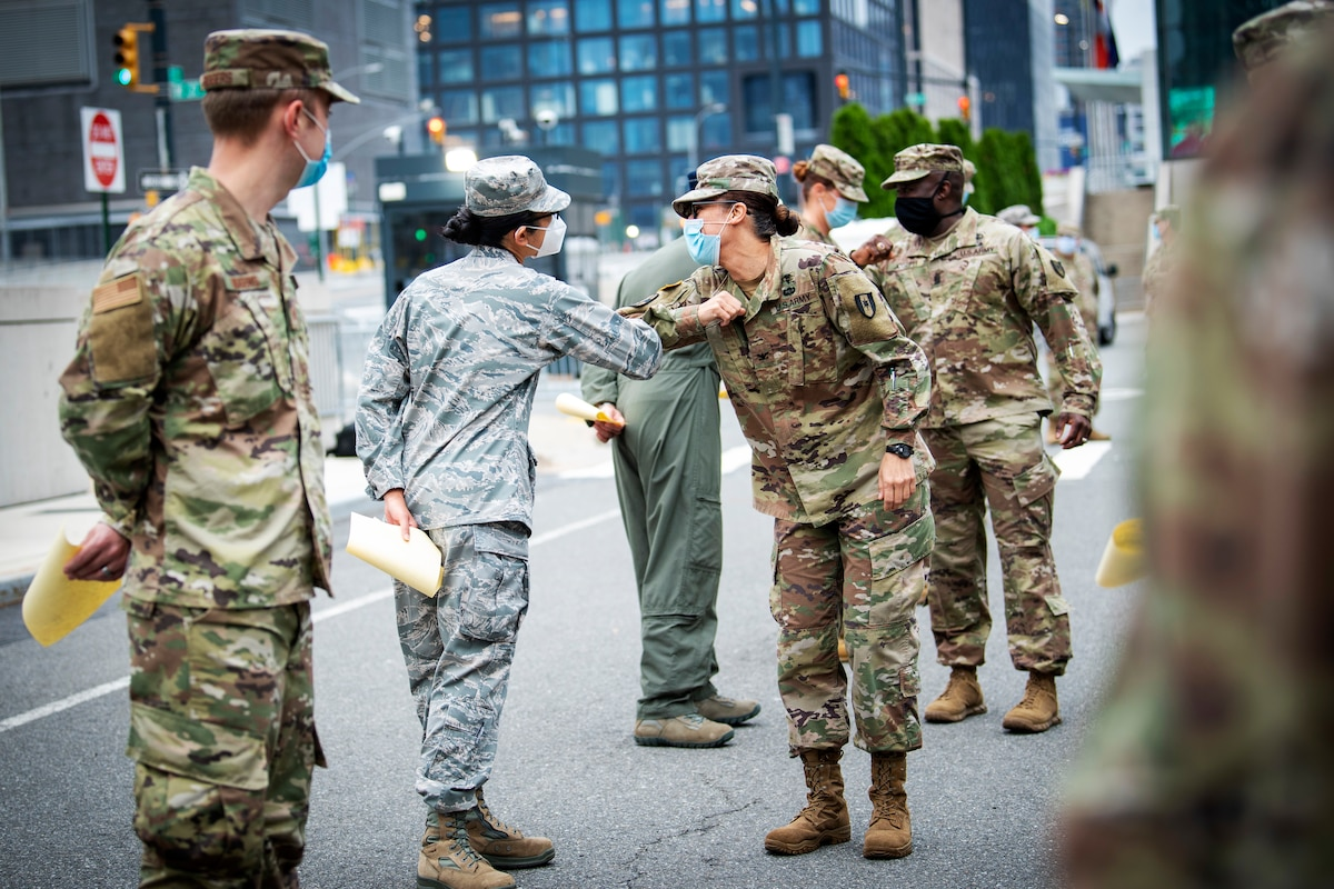 Service members wearing face masks and observing social distancing greet each other by touching elbows.