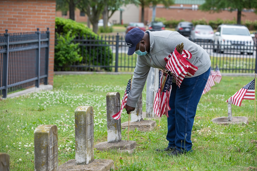 Veteran Employee Readiness Group Member Ricky Burroughs places a flag on the grave of a fallen service member at the Captain Ted Conaway Memorial Naval Cemetery.