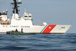 A low-profile go-fast vessel is shown next to the Coast Guard Cutter James.