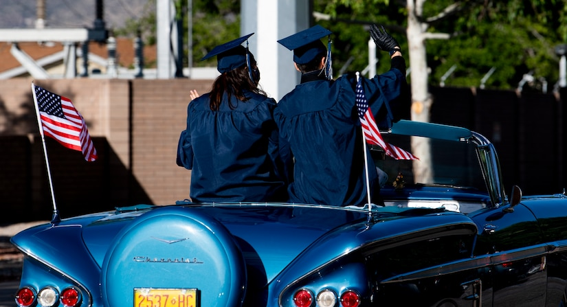 High school graduates ride in a graduation parade.