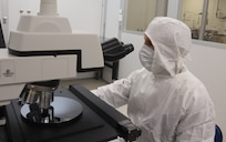 iles Owen, a metrologist with the Army Primary Standards Laboratory, counts aerosol particles deposited onto a silicon wafer in the APSL clean room. The measurement is part of a research project to calibrate particle counters using large aerosol particles in the size range of bacteria, with application to environmental monitors and biological defense sensors.