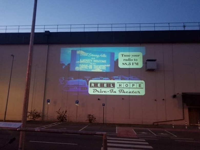 A projector displays radio directions to the crowd attending the 'Reel Hope Drive-in' theater Apr. 25 at Ramstein Air Base, Germany. Chaplain Portmann Werner, 693rd Intelligence, Surveillance, and Reconnaissance Group's head chaplain, converted the outside of their group's building and parking lot into the theater. (Courtesy Photo)