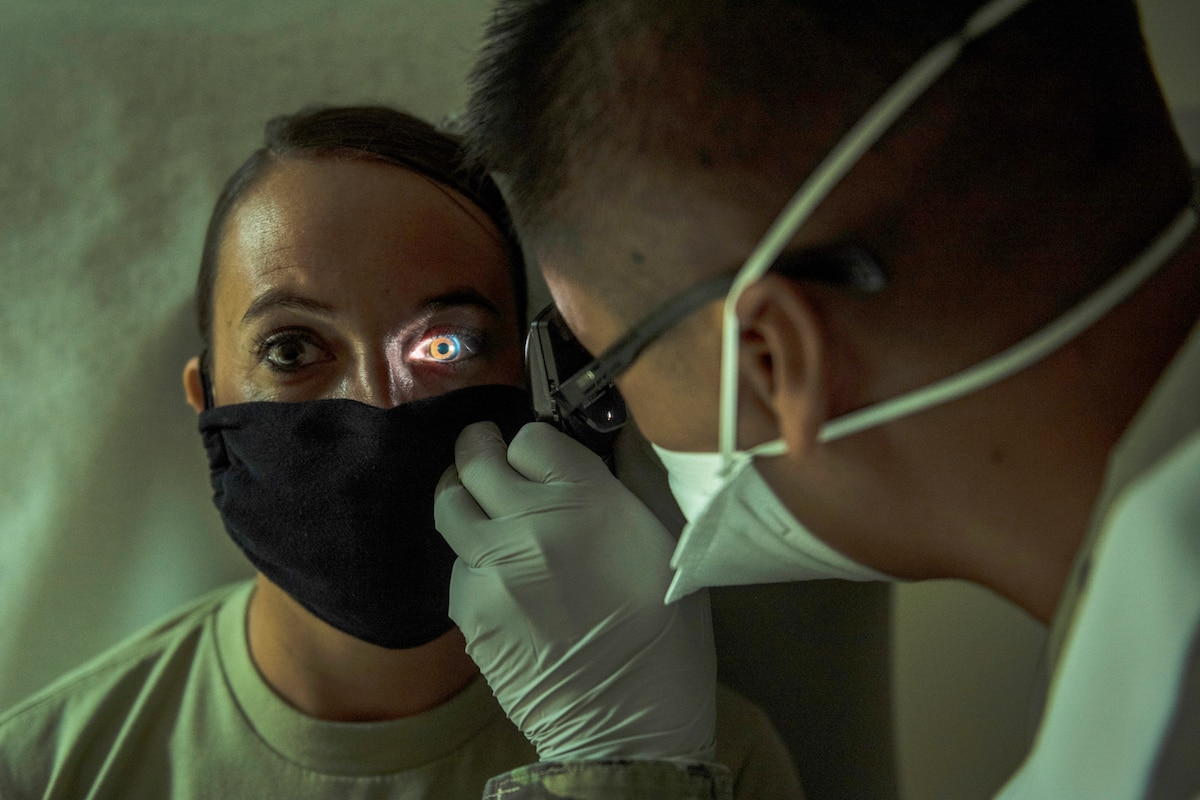 An Air Force physician in a face mask uses an instrument with a light to examine the eyes of a patient, who is also wearing a mask.