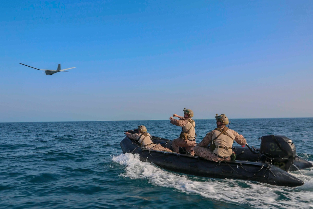 Three Marines ride in a combat rubber raiding craft; an unmanned aircraft system seen in the distance.